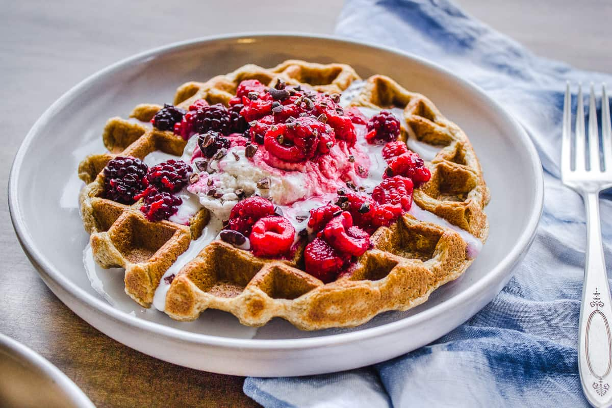 Overhead image of 3 Ingredient Oatmeal Waffle on a wooden table with a silver fork and blue & white napkin nearby. The waffle is decorated with raspberries, blackberries, coconut whipped cream and cacao nibs.