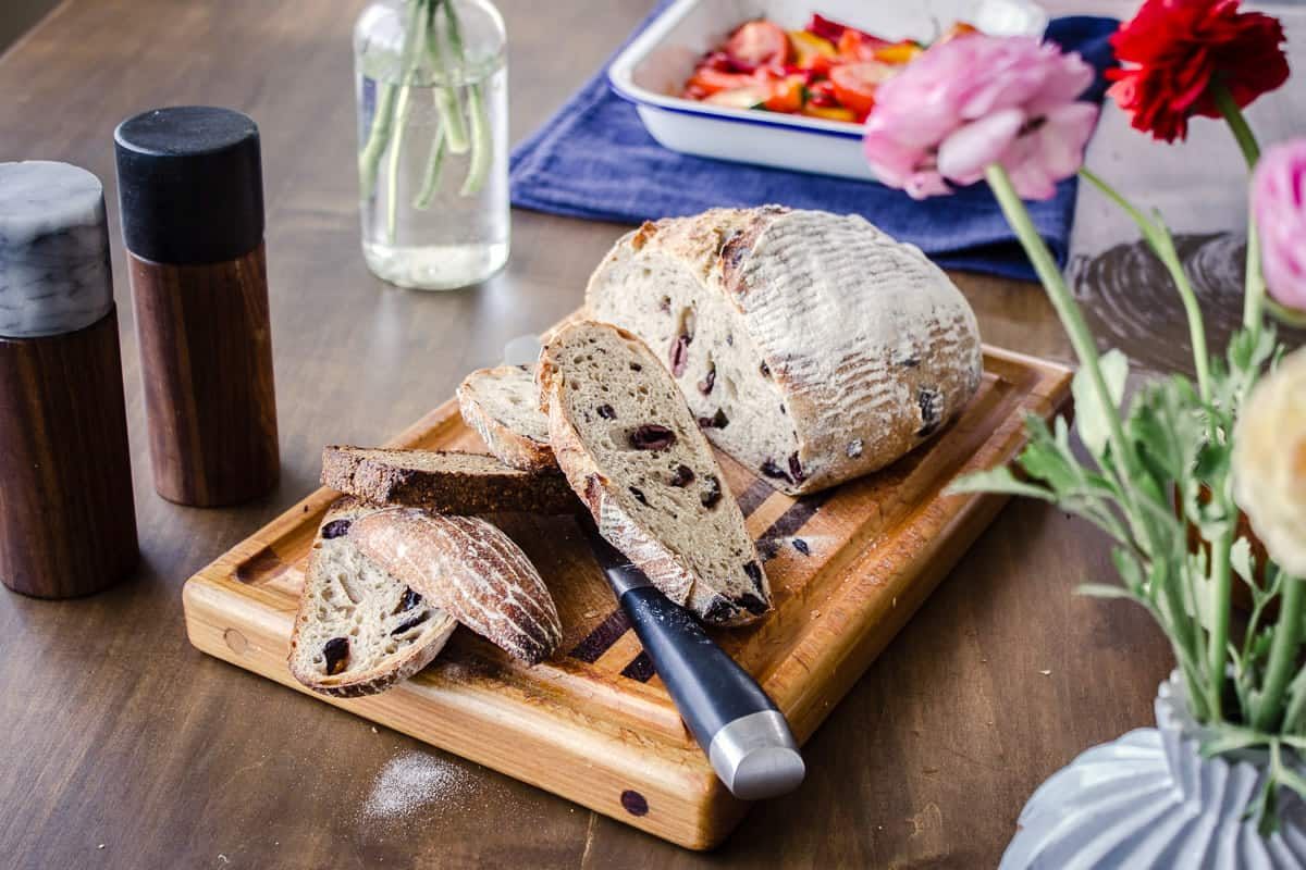 About & Contact - Vancouver with Love. Image shows a half-sliced loaf of sourdough olive bread on a chopping board. The board is surround by vases of flowers, a tray of colourful roasted vegetables and salt & pepper grinders.