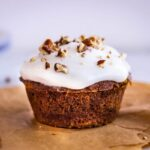 Close up image of Carrot Cake Muffins. Image shows a muffin on baking parchment, decorated with white frosting and pecans.