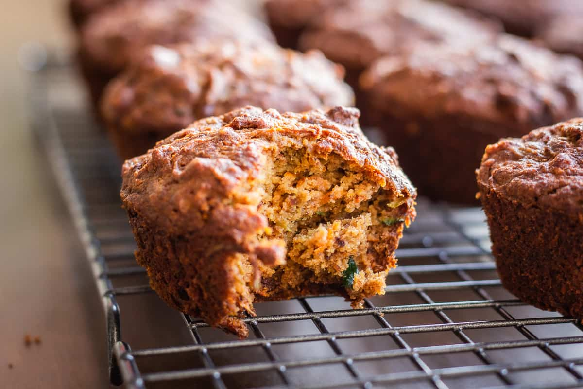 Close up image of Carrot Cake Muffins. Image shows a row of muffins on a wire cooling rack. One muffin has a bite taken out of it.