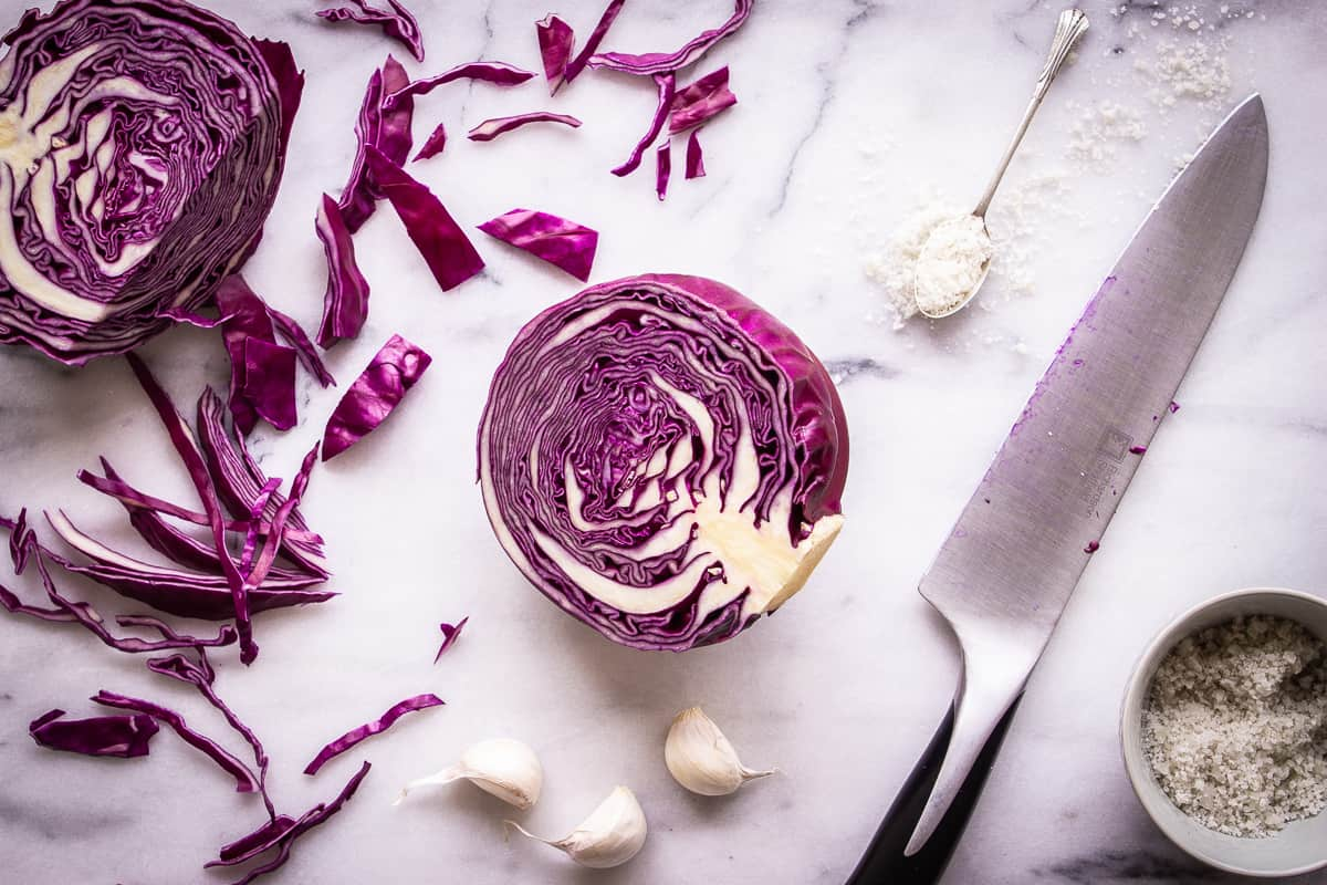 Overhead image shows ingredients needed for How to Make Sauerkraut. Shown are halves and slices of red cabbage, garlic cloves and sea salt. There is also a knife in the image.