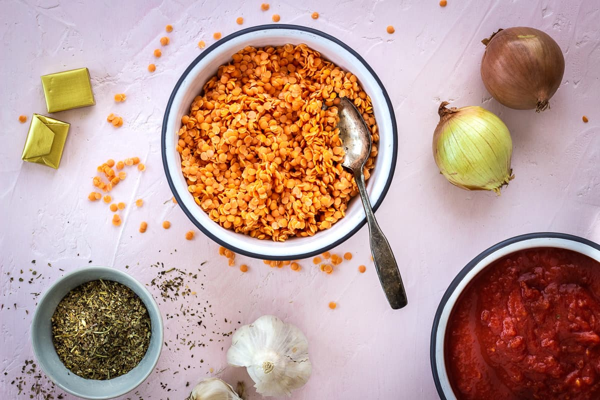 Overhead image of ingredients for Store Cupboard Lentil Bolognese on a light pink background. Image shows onions, garlic, red lentils, crushed tomatoes, dried herbs and stock cubes.
