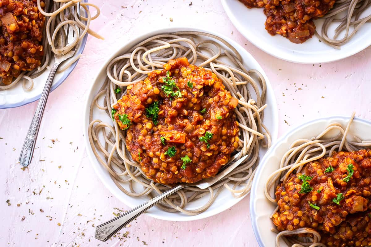 Overhead image of several plates of lentil bolognese with spaghetti on a light pink surface. Two of the plates have forks stuck in the spaghetti.