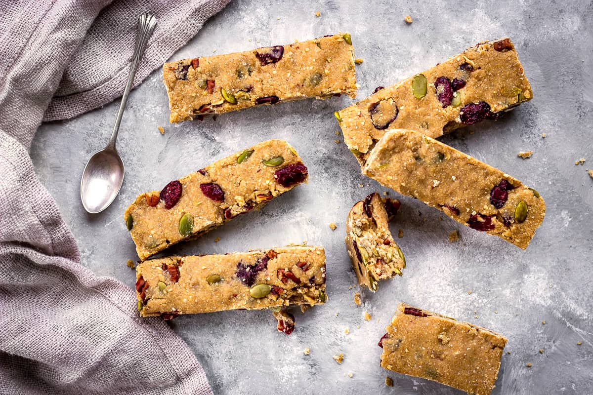 Image of vegan granola bars with cranberries, nuts and pumpkin seeds on a grey mottled background with a silver spoon and linen napkin.