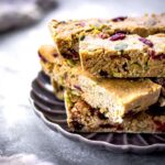 Image of vegan granola bars with cranberries, nuts and pumpkin seeds on a grey patterned plate.