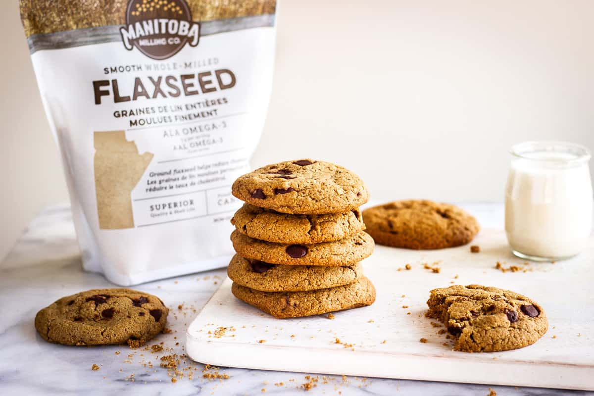 Image of Oatmeal Chocolate Chip Cookies. A stack of cookies is on a white wooden chopping board on a marble background, surrounded by more. Around them are some cookie crumbs and in the background is a glass of plant milk, and a bag of Manitoba Milling Company's Smooth Whole Milled Flaxseed.