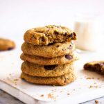 Close up image of Oatmeal Chocolate Chip Cookies. Cookies are on a white wooden chopping board on a marble background. Around them are some cookie crumbs and in the background is a glass of plant milk.