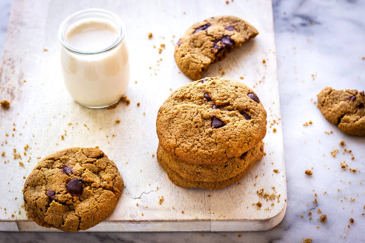 Image of Oatmeal Chocolate Chip Cookies. Cookies are on a white wooden chopping board on a marble background. Around them are some cookie crumbs and next to them is a glass of plant milk.