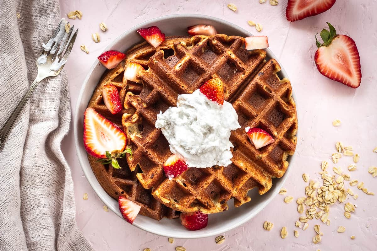 Overhead image of 3 Ingredient Oatmeal Waffles. A stack of waffles is on a grey plate on a light pink background. The waffles are decorated with strawberries and coconut whipped cream, and are surrounded by a silver spoon with cream on it, scattered oats, strawberry halves and a linen napkin.