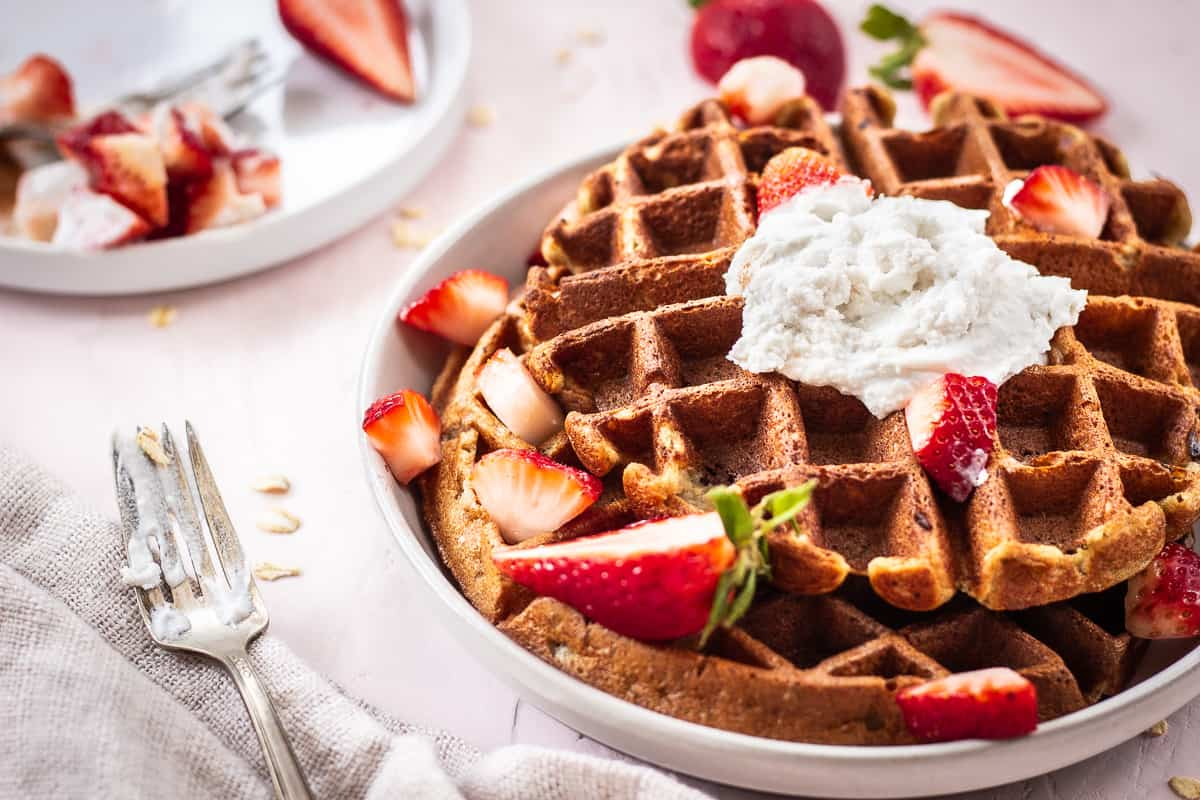 Close up image of 3 Ingredient Oatmeal Waffles. A stack of waffles is on a grey plate on a light pink background. The waffles are decorated with strawberries and coconut whipped cream, and are surrounded by a silver spoon with cream on it, scattered oats and a linen napkin. Another plate of strawberries is nearby.