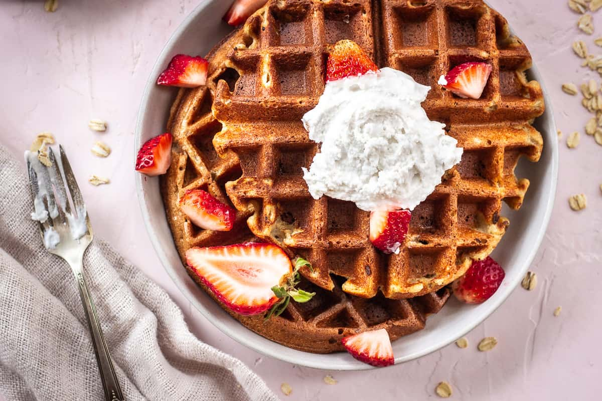 Overhead image of 3 Ingredient Oatmeal Waffles. A stack of waffles is on a grey plate on a light pink background. The waffles are decorated with strawberries and coconut whipped cream, and are surrounded by a silver spoon with cream on it, scattered oats and a linen napkin.