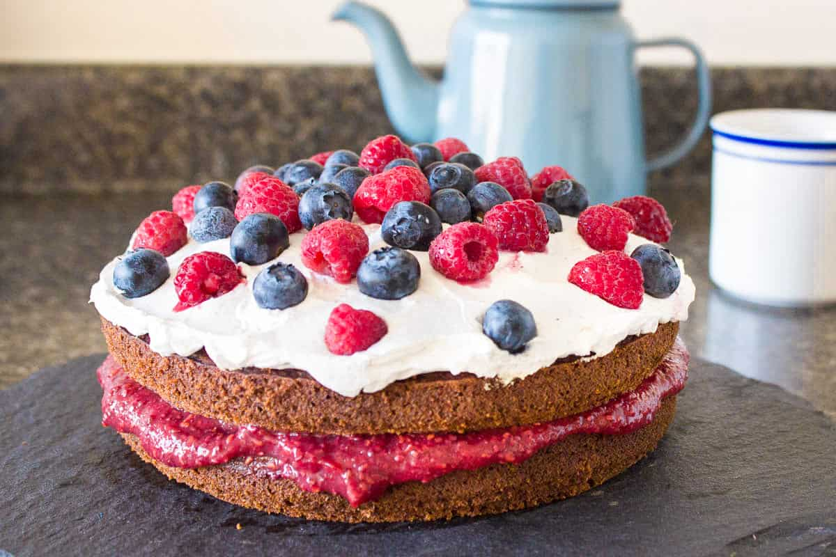 Image of dairy-free Victoria sponge. Cake is on a dark grey slate platter on a kitchen countertop and is decorated with raspberry jam, coconut whipped cream, blueberries and raspberries. In the background, a grey teapot and white striped cup are visible.