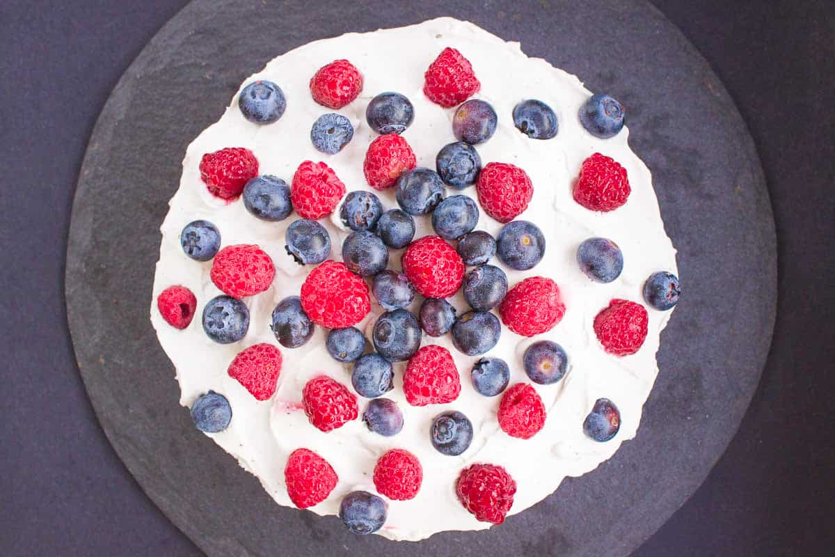 Overhead image of Victoria sponge cake. Cake is on a dark grey slate background and is decorated with coconut whipped cream, blueberries and raspberries.