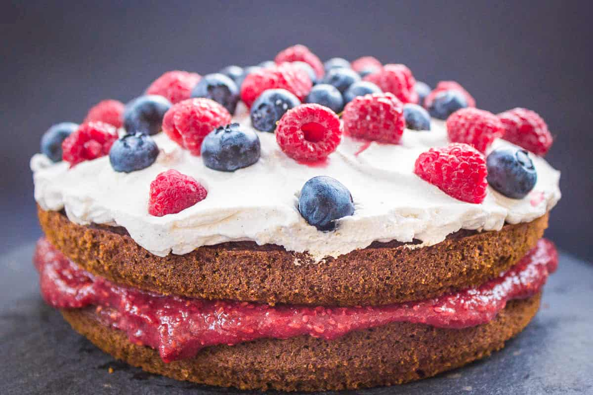 Image of Vegan Berry Sponge Cake. Cake is on a dark grey slate background and is decorated with raspberry jam, coconut whipped cream, blueberries and raspberries.