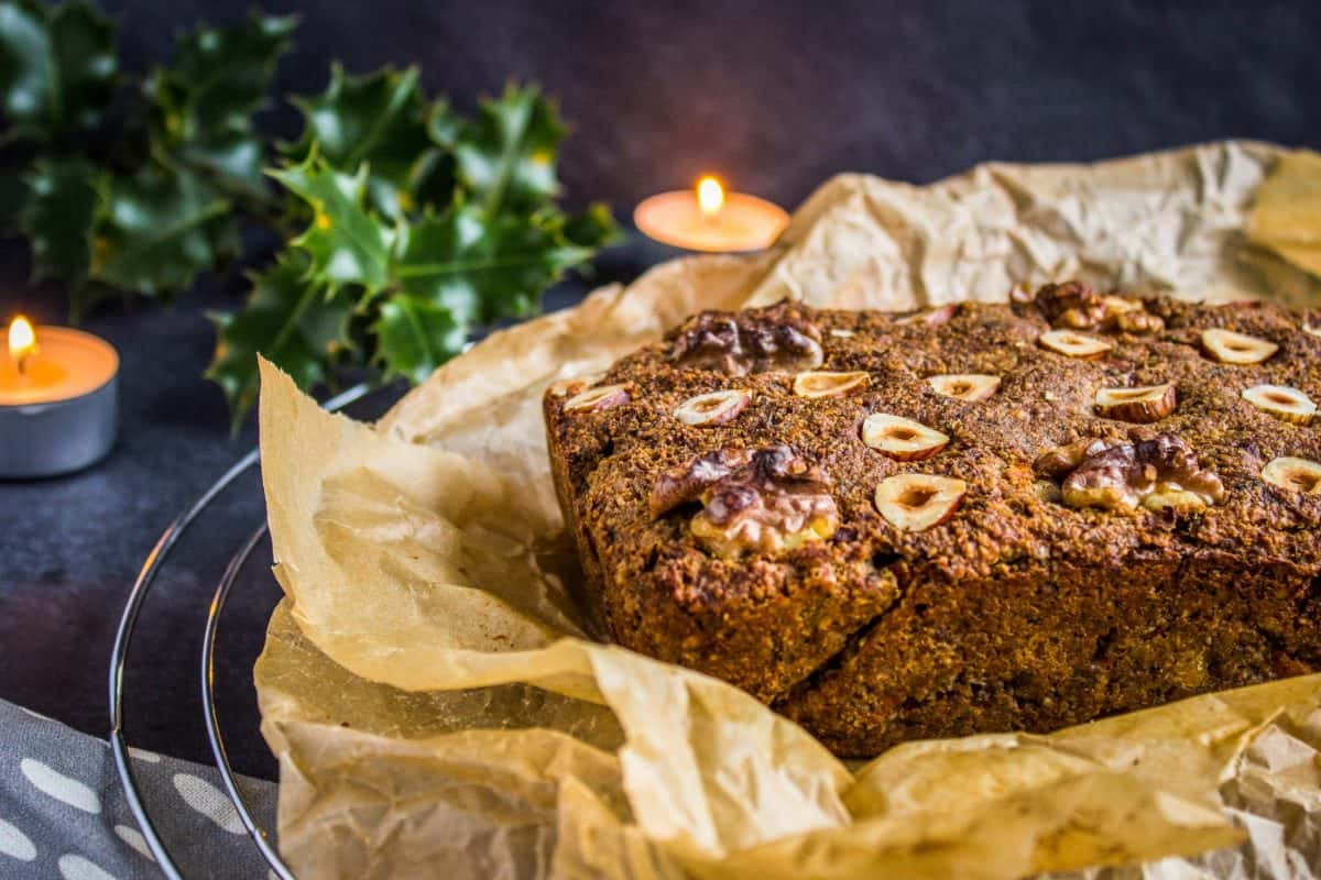 Closeup view of Classic Vegan Nut Roast. Nut roast is on a wire cooling rack, surrounded by a grey napkin, candles and holly/pine branches.