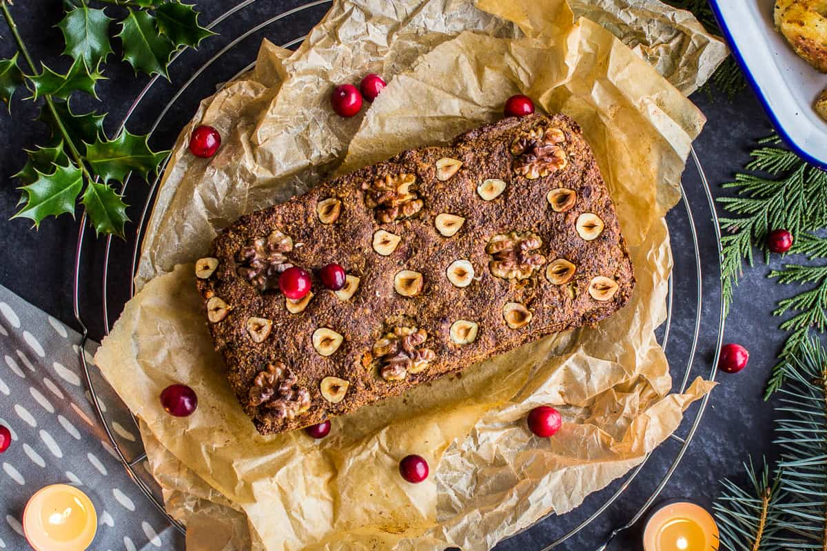 Overhead view of Classic Vegan Nut Roast. Nut roast is on a wire cooling rack, surrounded by a grey napkin, candles and holly/pine branches. It is sprinkled with cranberries and there is a dish of roast potatoes nearby.