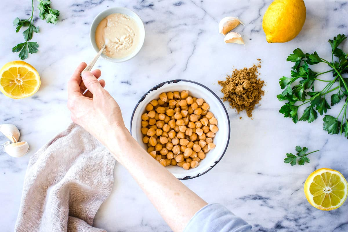 Overhead view of chickpea dip ingredients including chickpeas, lemons, parsley and tahini, accompanied by woman's hand holding tahini spoon.