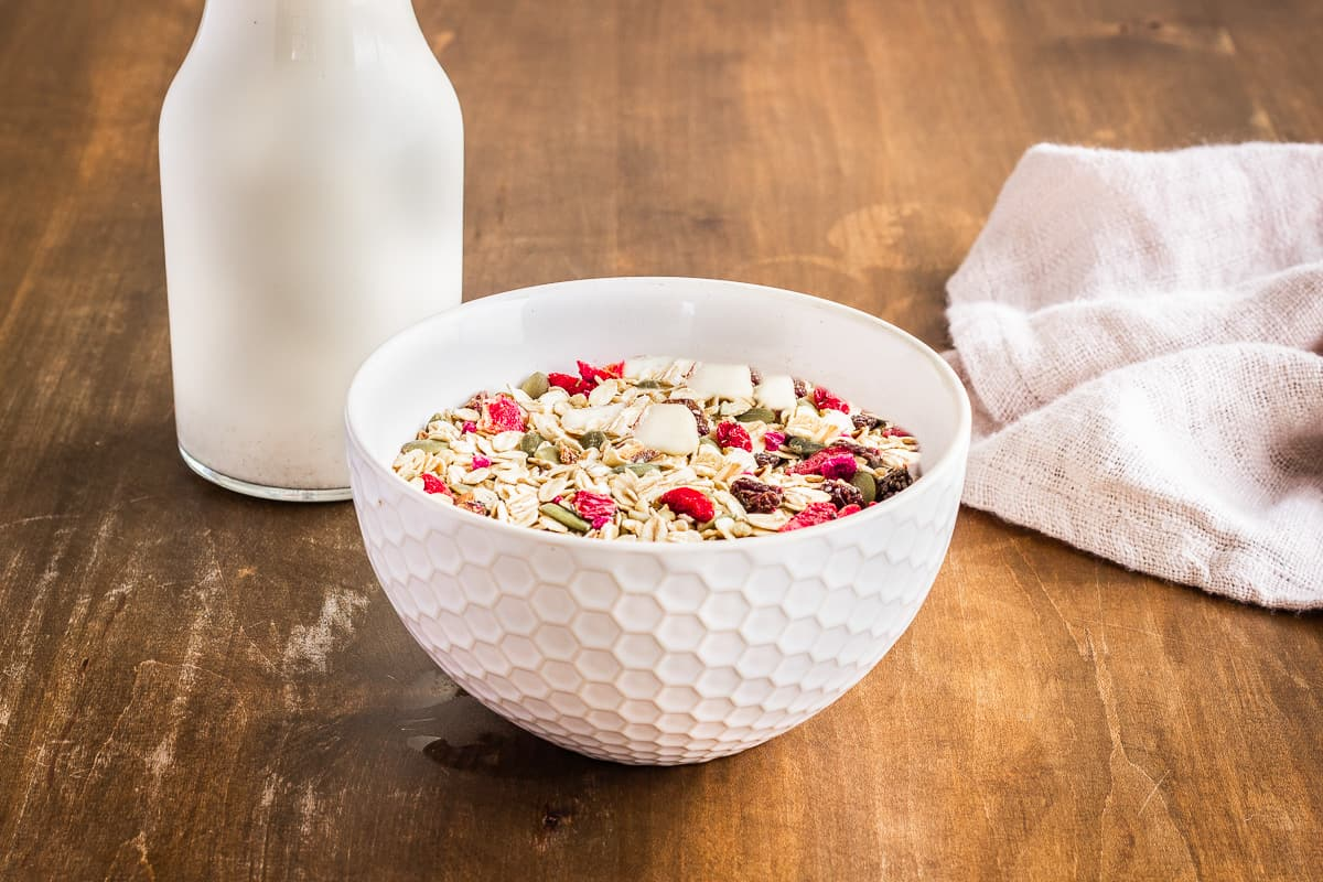 Image shows a bowl of muesli with raspberries and goji berries on a wooden table. Behind it is a linen napkin and a bottle of homemade dairy-free beverage.