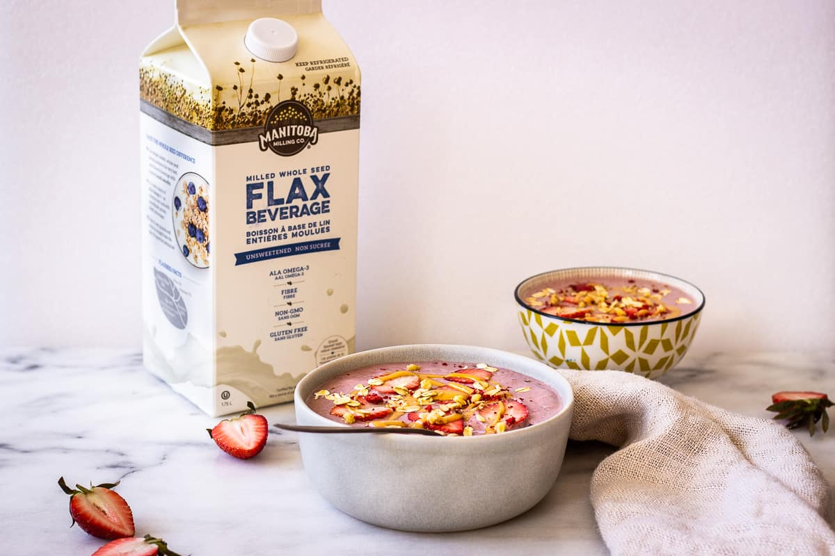 Image shows two pink smoothie bowls on a marble surface, decorated with strawberries, peanut butter and oats. In the background is a carton of Manitoba Milling Company's Unsweetened Flax Beverage.