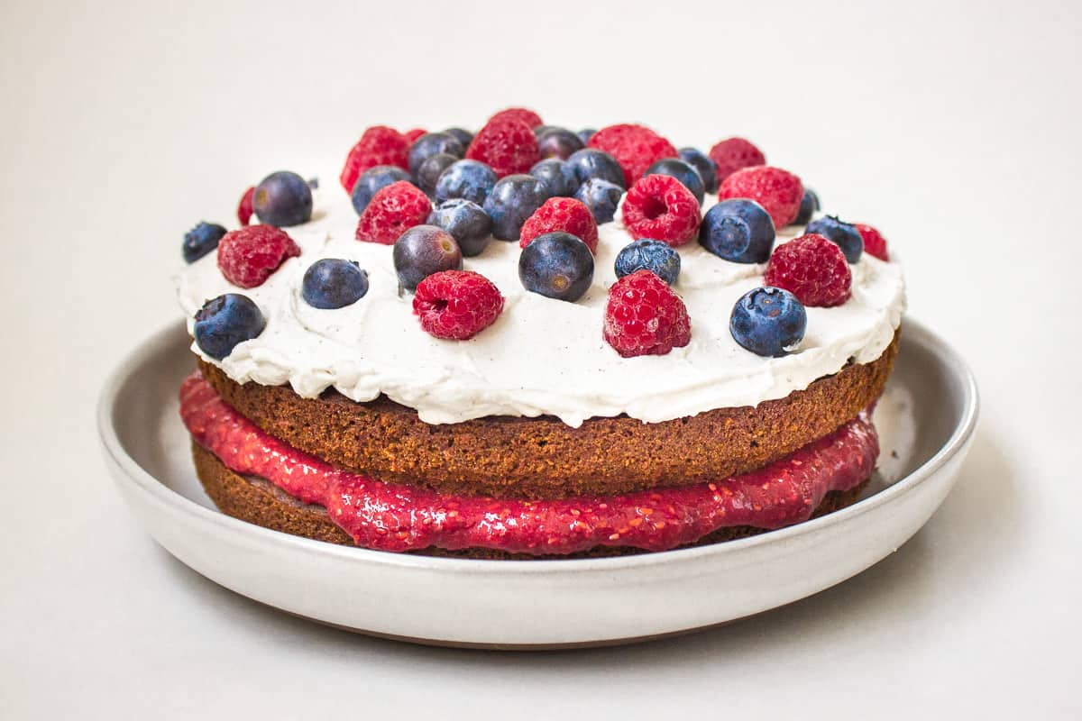 Image of Vegan Berry Sponge Cake. Cake is on a light grey plate on a white background and is decorated with raspberry jam, coconut whipped cream, blueberries and raspberries.