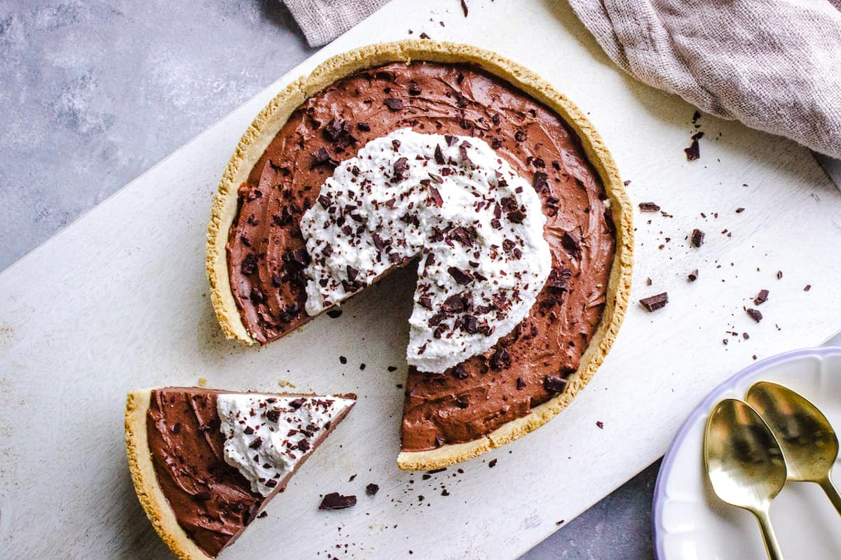 Overhead shot of 8-Ingredient Vegan Chocolate Pie topped with whipped coconut cream and shaved chocolate.