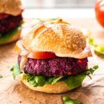 Close up image of Easy Beet & Black Bean Burger on parchment paper. The burger is surrounded by lettuce leaves and tomato slices, and there is a second burger in the background.