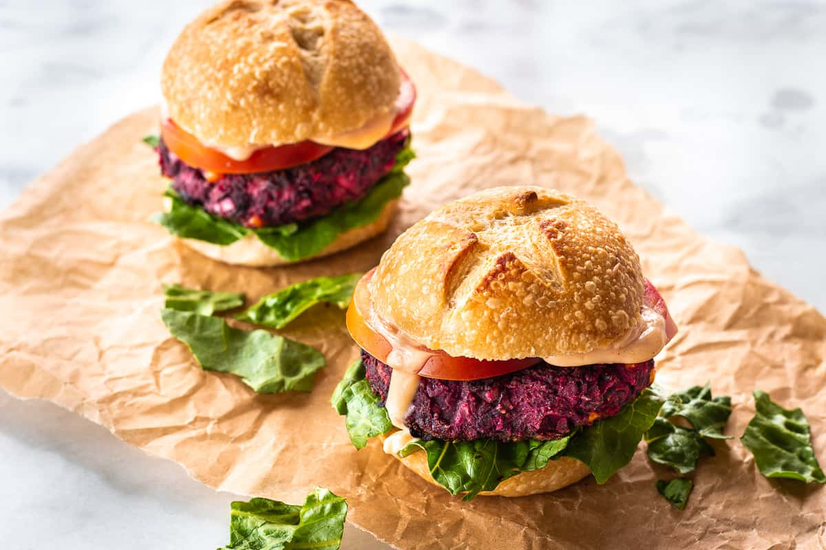 Two Easy Beet & Black Bean Burgers on parchment paper. They are surrounded by lettuce leaves and are resting on a white marble surface.
