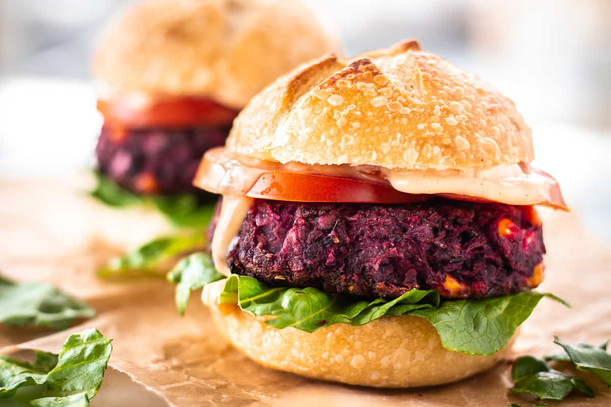 Close up image of Easy Beet & Black Bean Burger on parchment paper. The burger is surrounded by lettuce leaves, and there is a second burger in the background.