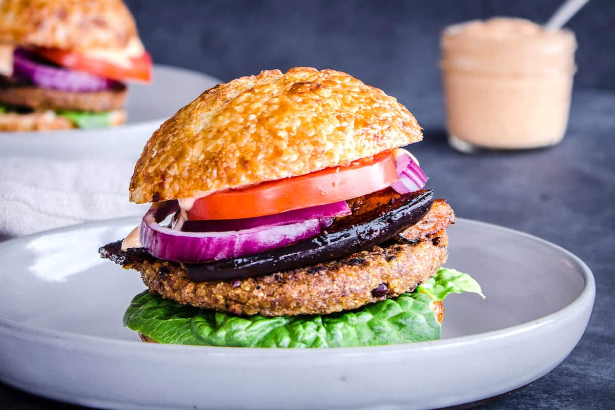Image shows Smoky Eggplant Bean Burger on a grey plate layered with slices of tomato, red onion, smoky eggplant and lettuce. In the background is another burger and a jar of vegan garlic mayo.
