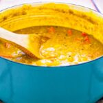 Image of Winter Warming Dhal in blue enamel saucepan on tiled surface. The dhal is a deep golden yellow with carrots in it. There is a wooden spoon in the saucepan, and it sits on a potholder.