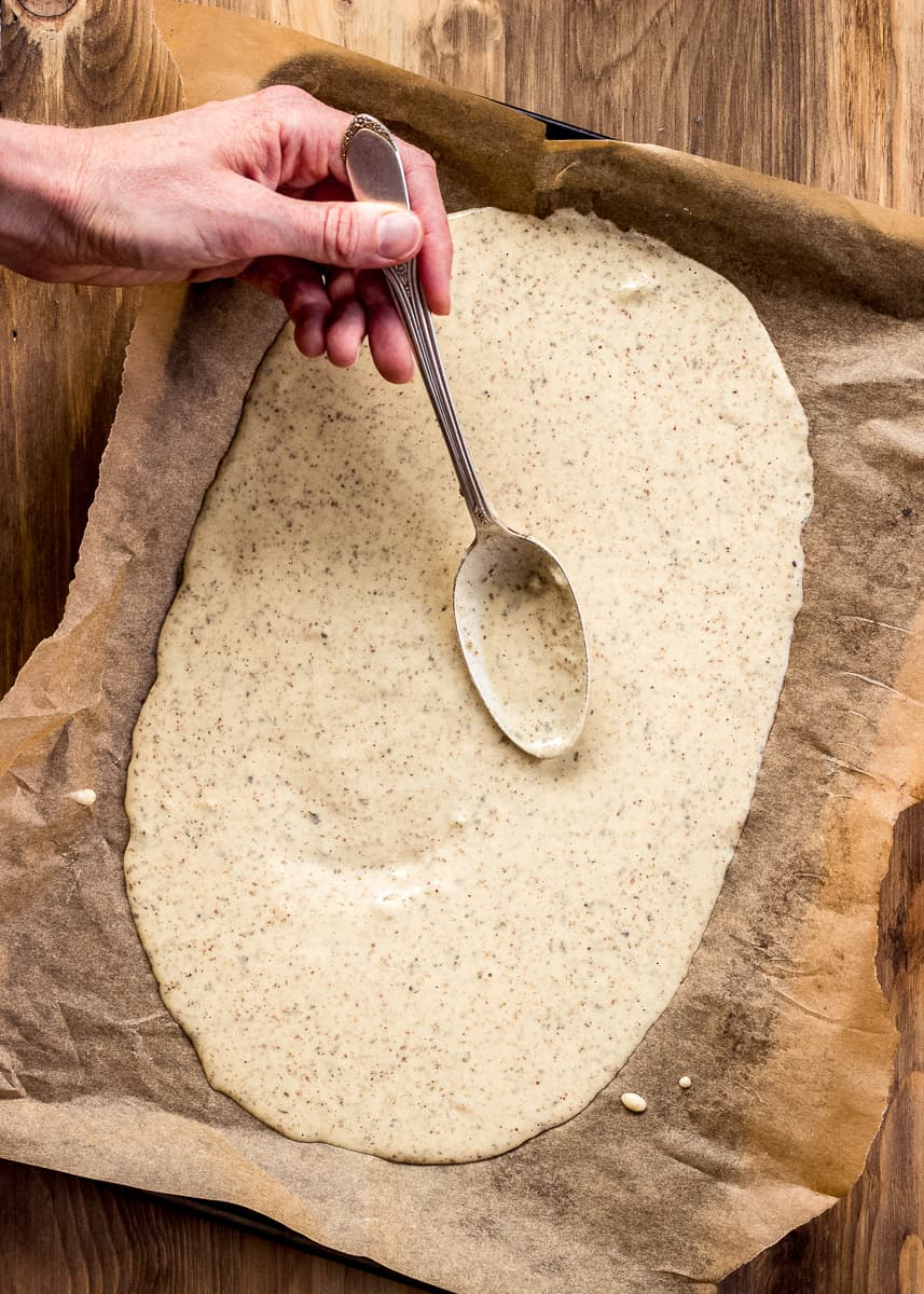 Overhead image shows uncooked pizza crust batter being spread onto a baking sheet covered in baking parchment by a woman's hand holding a spoon.
