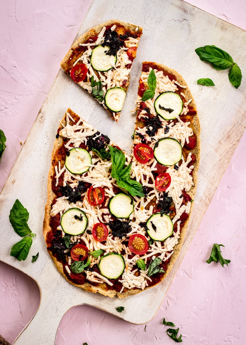 Overhead image shows Chickpea Flour Pizza Crust on a white chopping board on a pink background. The pizza is topped with tomato sauce, vegan cheese, zucchini, tomatoes, spinach and basil. A slice has already been cut from it.