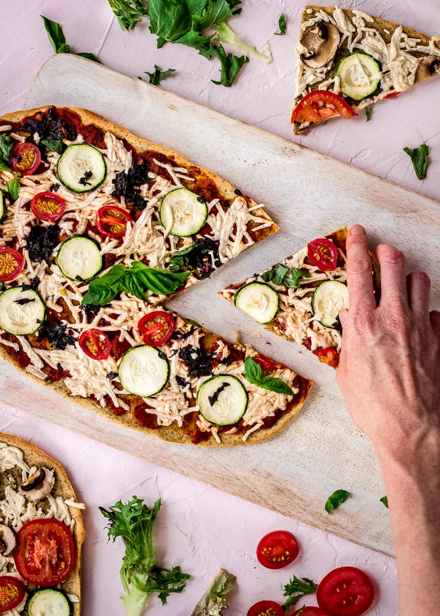 Overhead image shows Chickpea Flour Pizza Crust on a white chopping board on a pink background. The pizza is topped with tomato sauce, vegan cheese, zucchini, tomatoes, spinach and basil. A slice has already been cut from it, and a woman's hand is reaching for it. The pizza is surrounded by a pizza more slices of pizza, salad leaves and tomato slices.