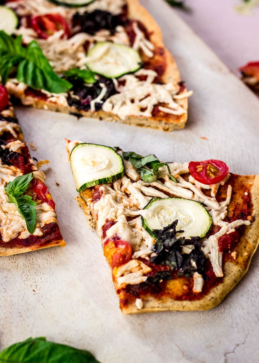 Close up image shows Chickpea Flour Pizza Crust on a white chopping board on a pink background. The pizza is topped with tomato sauce, vegan cheese, zucchini, tomatoes, spinach and basil. A slice has already been cut from it.