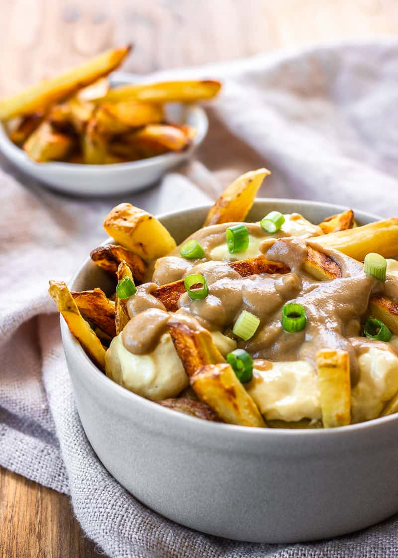 Image of Easy Vegan Poutine in grey bowl on a linen napkin. Poutine is decorated with cheese curds, gravy and green onions.