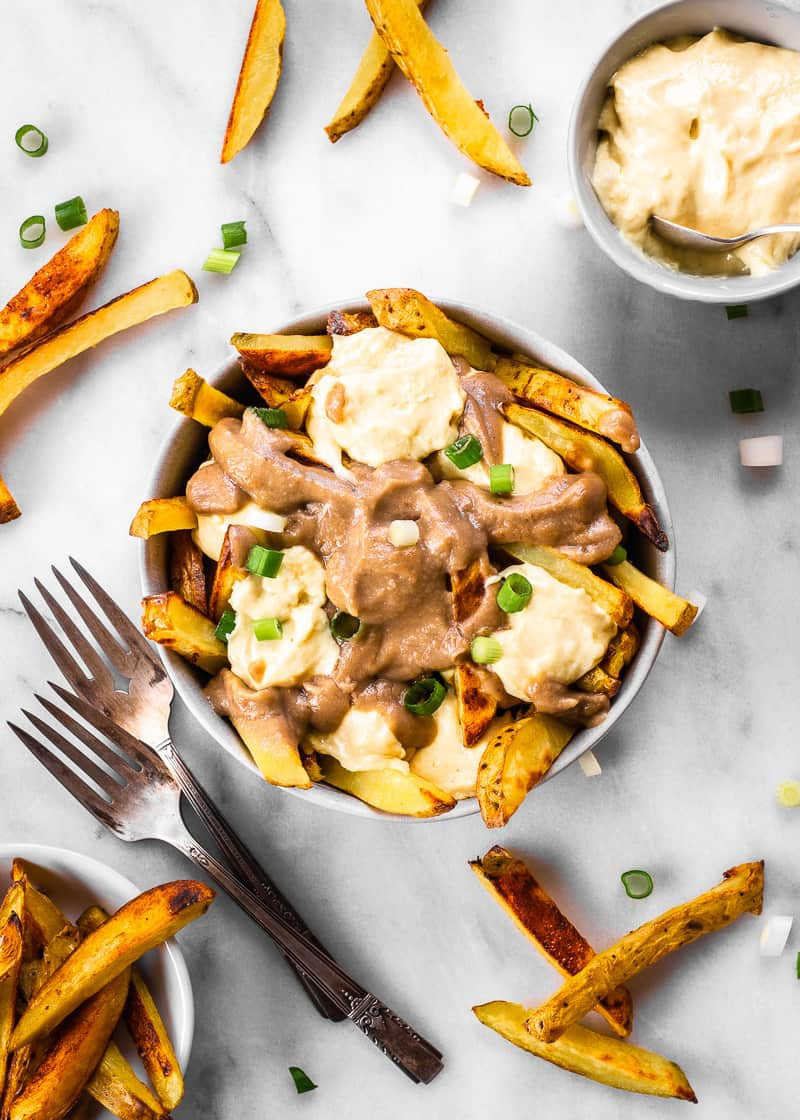 Overhead image of Easy Vegan Poutine. Poutine is decorated with cheese curds, gravy and green onions and is surrounded by extra fries, a bowl of cheese curds and some forks.