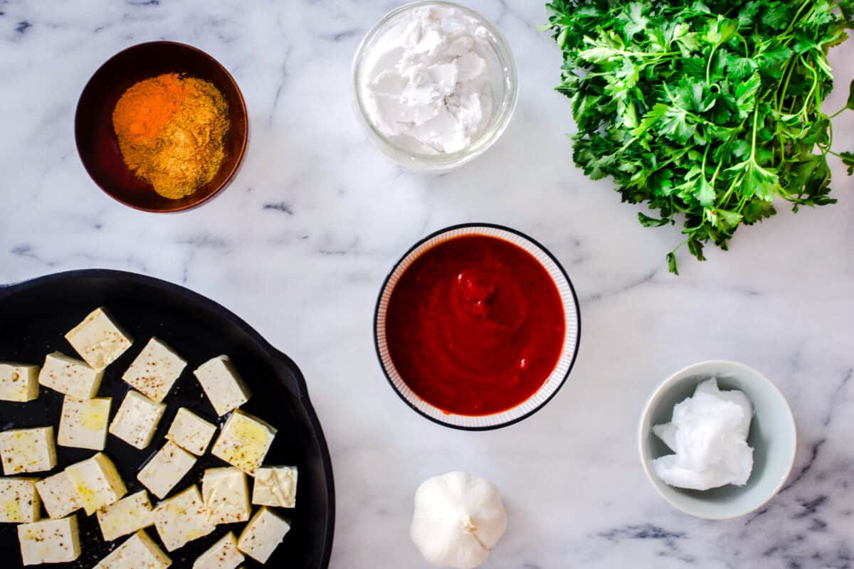 Overhead images shows various ingredients on a white marble background: a cast iron pan of tofu cubes, a bowl of turmeric, a bunch of cilantro, a jar of coconut milk, some coconut oil, crushed tomatoes and a bulb of garlic.