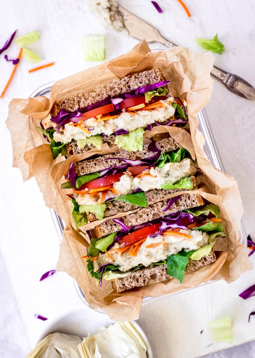Overhead image of White Bean & Artichoke Vegan Sandwiches in a parchment paper-lined container on a white background. They are surrounded by a dish of artichokes, a silver butter knife and some vegetable pieces.