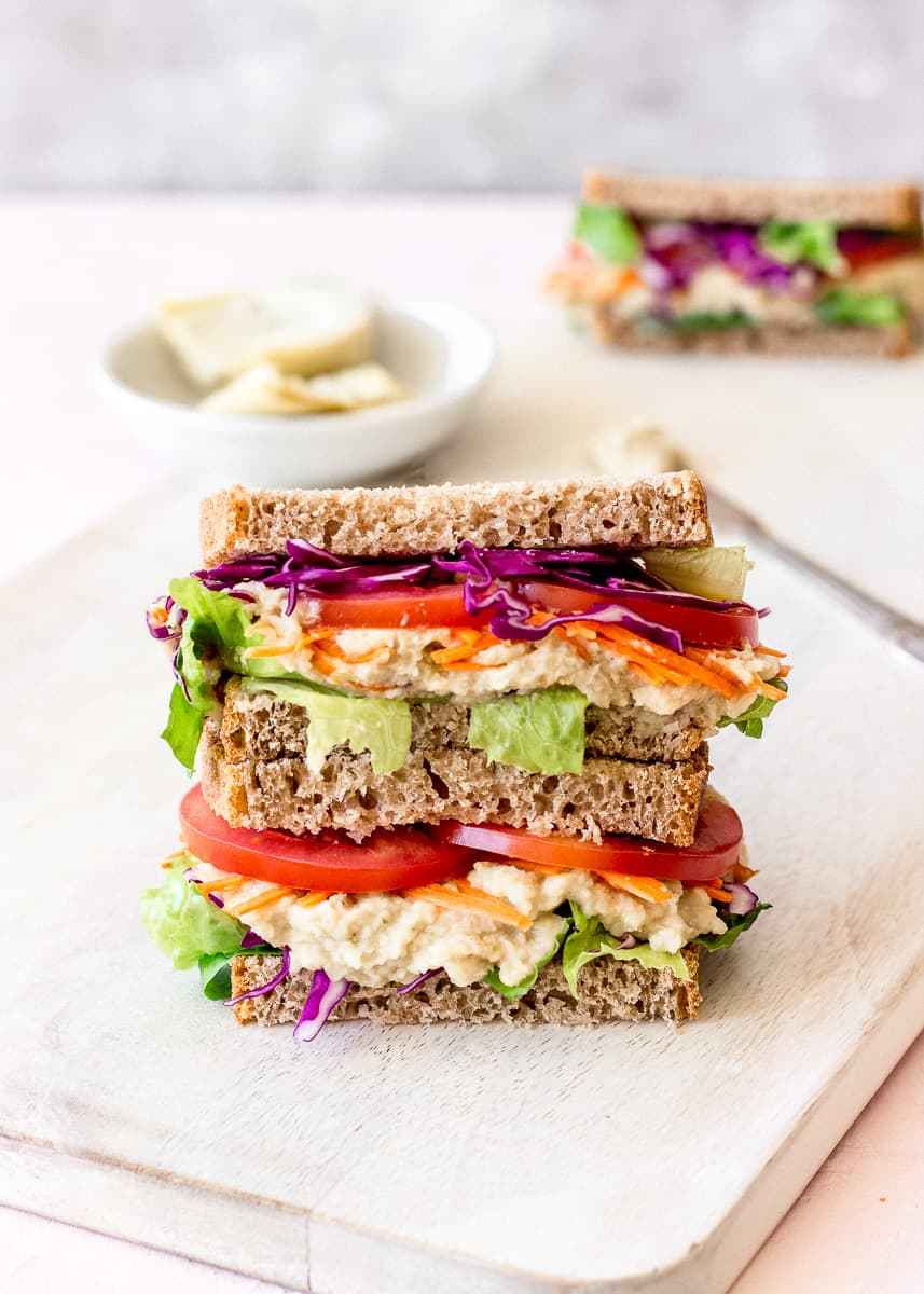 Close up image of a brightly coloured sandwich on a white chopping board. In the background is a dish of artichokes, a silver butter knife and a second sandwich.