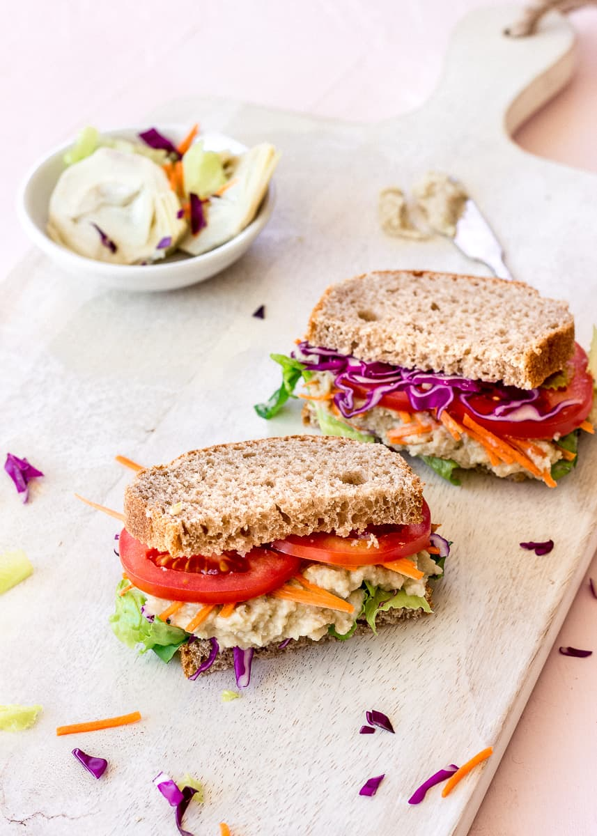 Side image of two sandwiches on a white wooden chopping board. The sandwiches are filled with brightly coloured vegetables and spread, and behind them is a dish of artichokes and other vegetables.