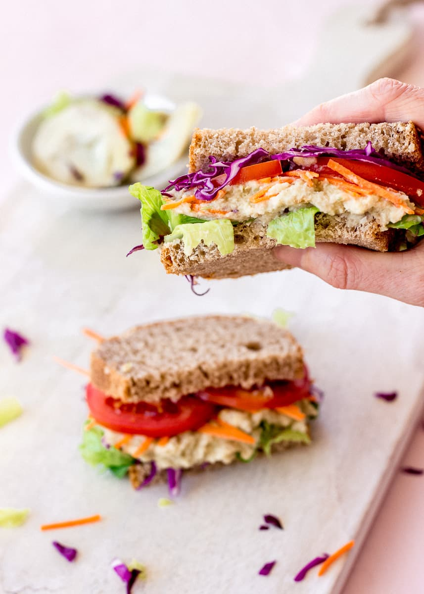 Image of a woman's hand holding a White Bean & Artichoke Vegan Sandwich. In the background there is a dish of artichokes and another sandwich.