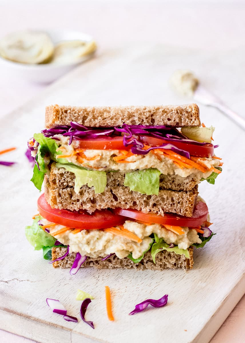 Close up image of White Bean & Artichoke Vegan Sandwich on a white chopping board. In the background is a dish of artichokes, a silver butter knife and some vegetable pieces.