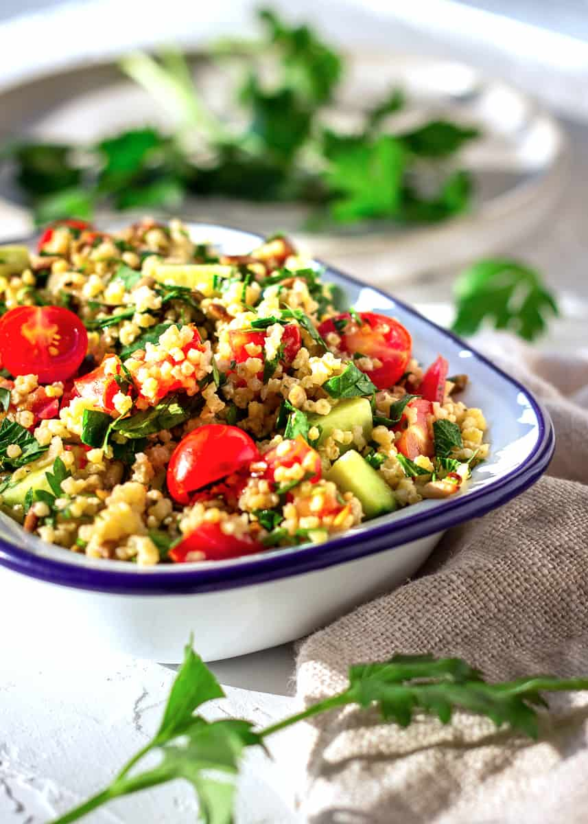 Image shows one bowl of Gluten-free Millet Tabbouleh on a white plaster background. The tabbouleh contains cucumber, parsley and cucumber. Behind it is a plate with scattered parsley leaves.