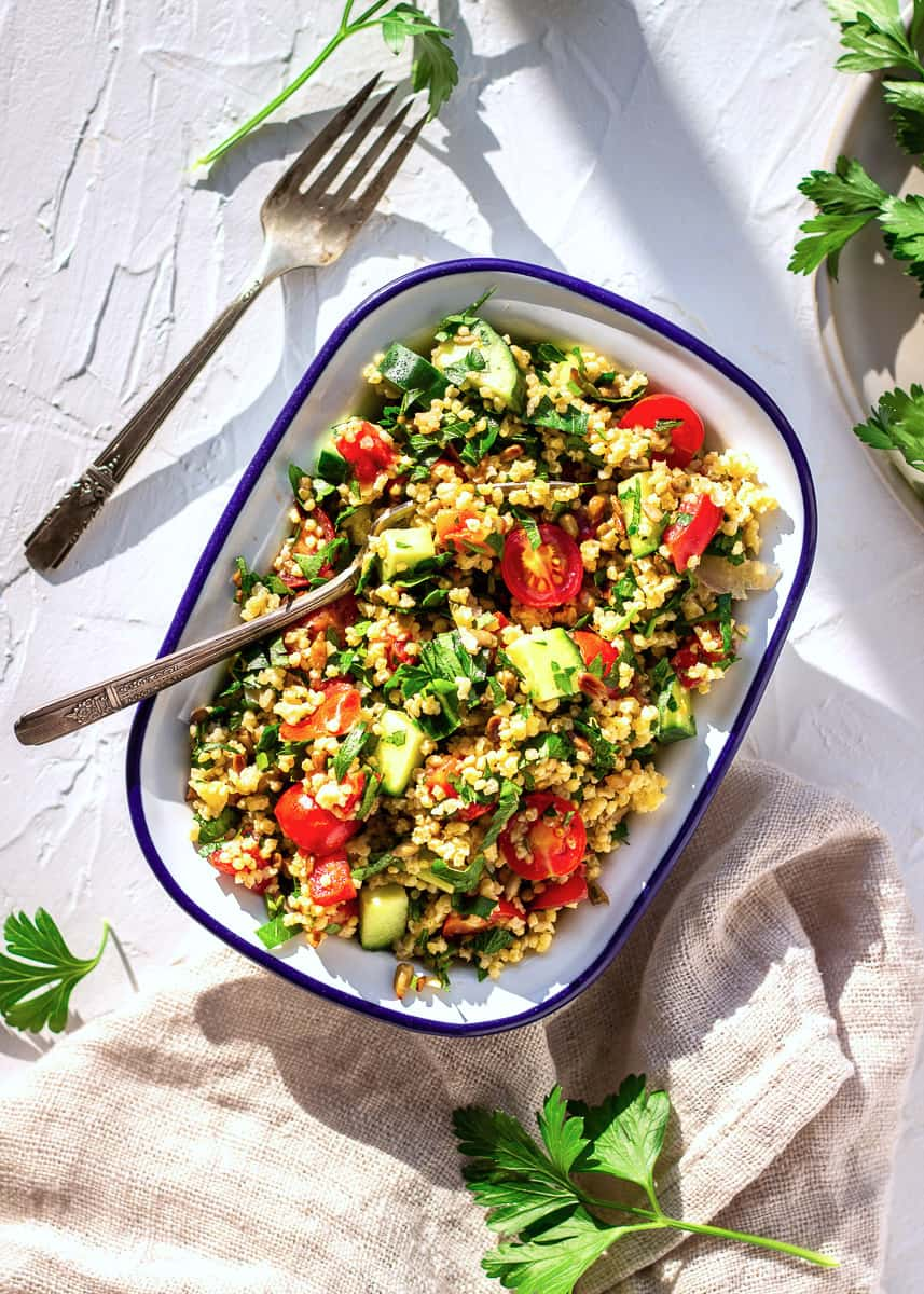 Overhead shot of one white enamel bowl of Middle Eastern salad on a white plaster background surrounded by forks, parsley leaves and a napkin. The salad contains tomatoes, parsley, millet and cucumber.