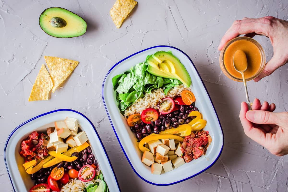 Overhead shot of vegan burrito bowls on a grey plaster background, surrounded by avocado, salsa and tortilla chips. A woman's hand is holding a jar of dressing with a spoon.
