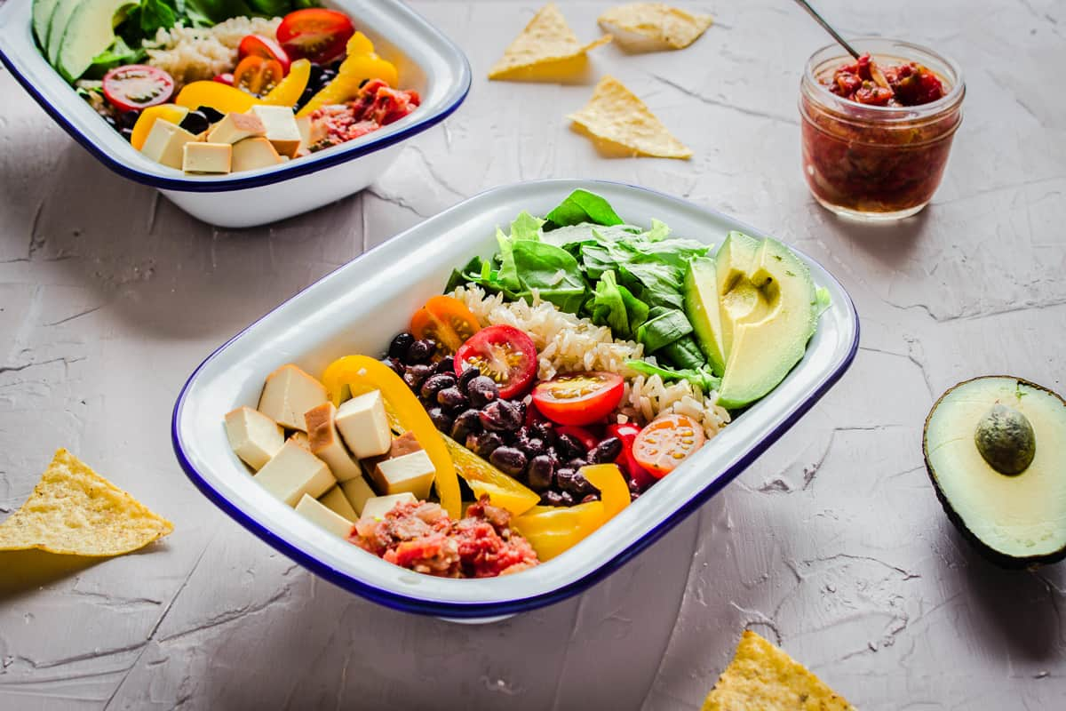 Close up shot of Healthy Burrito Bowls on a grey plaster background, surrounded by avocado, salsa and tortilla chips. One bowl is in the foreground and another is in the background.