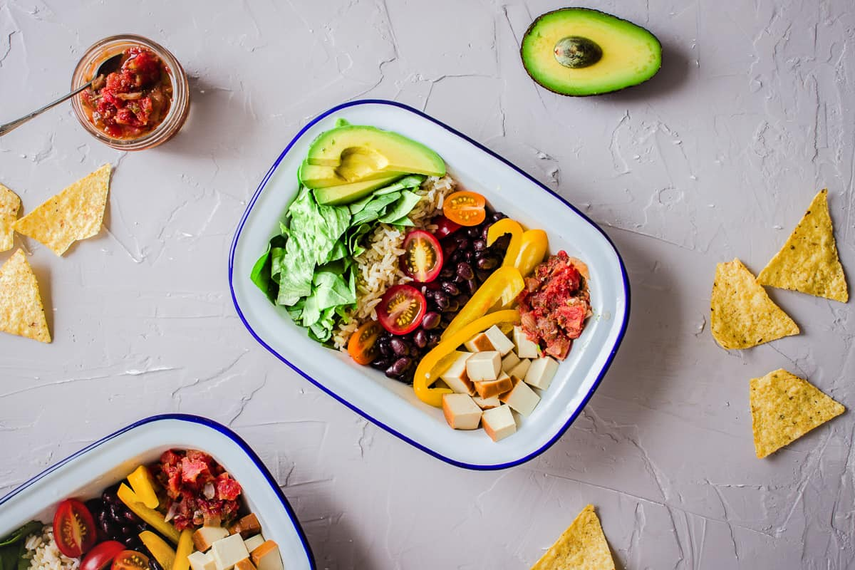 Overhead shot of vegan Mexican bowls on a grey plaster background, surrounded by avocado, salsa and tortilla chips. A woman's hand is holding a jar of dressing with a spoon.Overhead shot of Healthy Burrito Bowls on a grey plaster background, surrounded by avocado, salsa and tortilla chips.