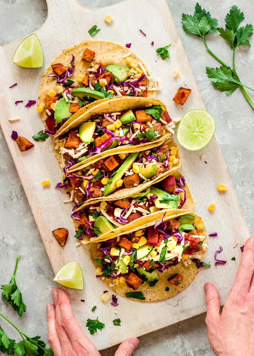 Overhead image of Roasted Sweet Potato Tacos on a white wooden chopping board. The tacos are decorated with red cabbage, avocado and sweetcorn. A woman's hands hold the chopping board and there are wedges of lime and cilantro leaves surrounding the tacos.