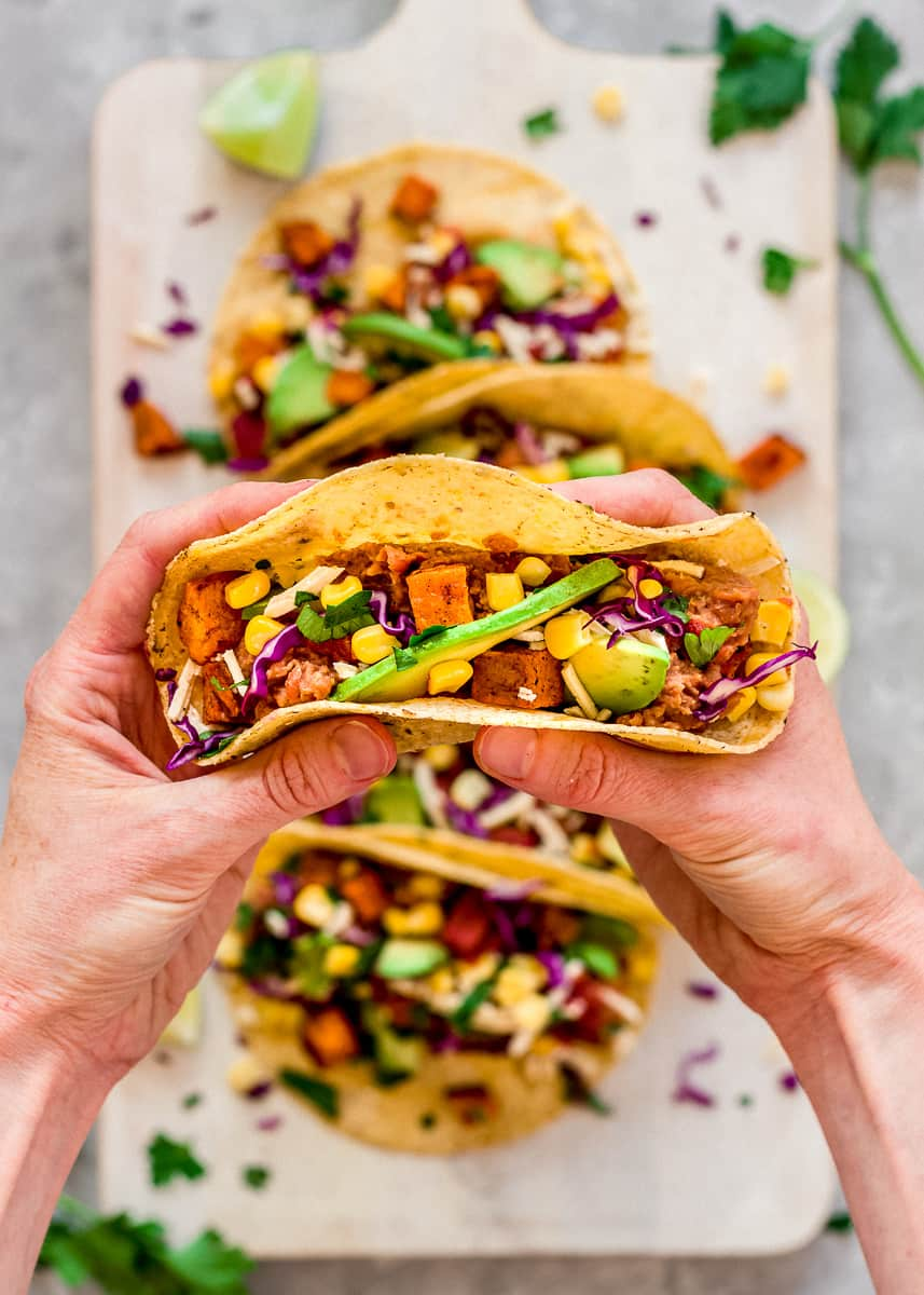 Close up overhead image of Roasted Sweet Potato Tacos on a white wooden chopping board. In the foreground, a woman's hands hold a taco decorated with sweetcorn, red cabbage, avocado and roasted sweet potato cubes.
