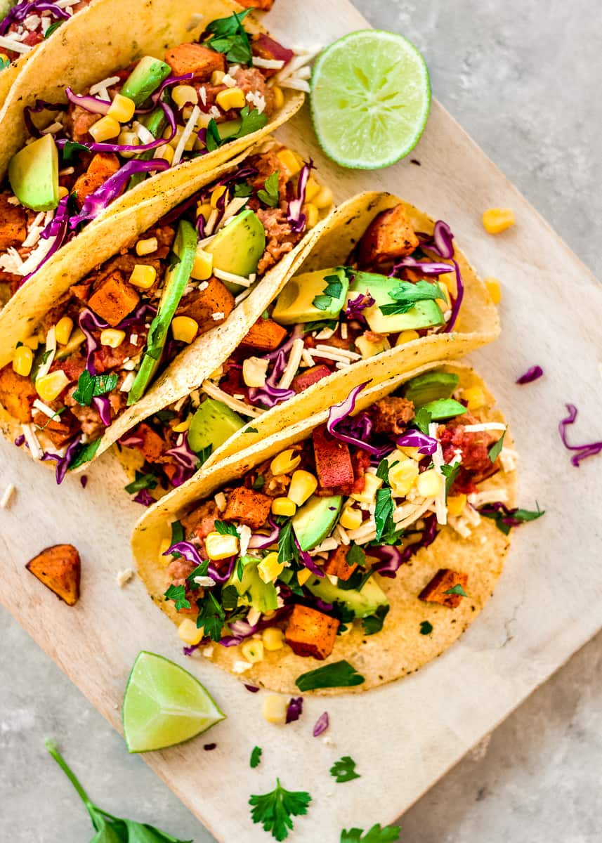 Partial overhead image of Roasted Sweet Potato Tacos on a white wooden chopping board. The tacos are decorated with red cabbage, avocado and sweetcorn. There are wedges of lime and cilantro leaves surrounding the tacos.